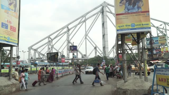 pedestrians and traffic move along a road near the howrah bridge in kolkata, india, on friday, may 26 feet of pedestrians are seen walking on a road... - cantilever bridge stock videos & royalty-free footage