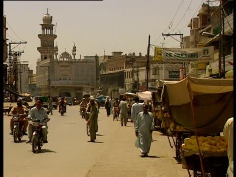 pedestrians and traffic move along a road, pakistan. - pakistan stock-videos und b-roll-filmmaterial