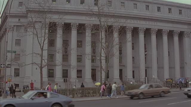 pedestrians and traffic move in front of a united states court house building. - federal building stock videos & royalty-free footage