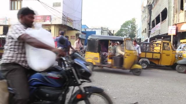 Pedestrians and traffic moving down the market streets in Hyderaba India on March 11th Wide shot of trucks car bicycles motorcycles carts and...
