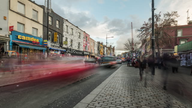Pedestrians and traffic moving rapidly past a parade of shops on Camden High Street