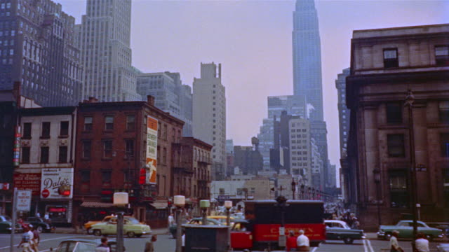 1955 ws pedestrians and traffic on 33rd street and 8th avenue with empire state building in background / old penn station visible on right / new york city - new york city penn station stock videos and b-roll footage