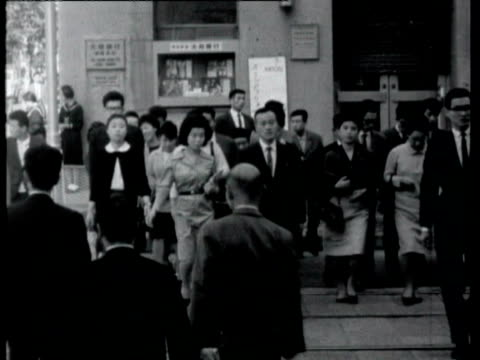 vídeos de stock, filmes e b-roll de pedestrians and traffic on busy city street including cyclist weaving through traffic pedestrians and traffic in tokyo on october 16 1964 in tokyo... - 1964