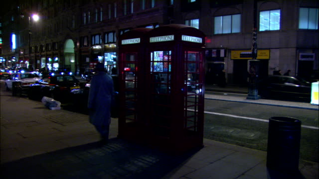 stockvideo's en b-roll-footage met pedestrians and traffic pass a phone booth. - telefooncel