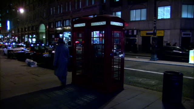 pedestrians and traffic pass a phone booth. - telefonkiosk bildbanksvideor och videomaterial från bakom kulisserna