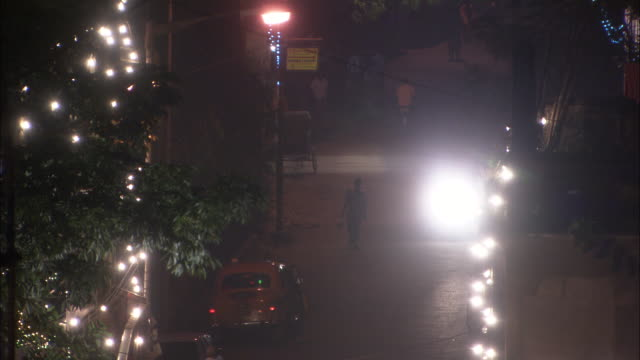 vídeos de stock, filmes e b-roll de pedestrians and traffic pass along busy street during diwali hindu festival of lights mumbai available in hd. - festival tradicional