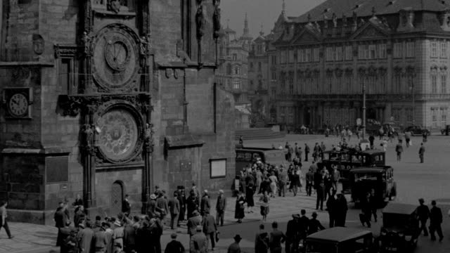 pedestrians and traffic pass an old cathedral in prague, czechoslovakia. - stare mesto stock videos & royalty-free footage