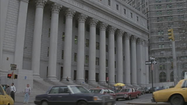 pedestrians and traffic pass in front of a united states courthouse in new york. - courthouse stock videos & royalty-free footage
