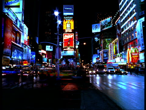 pedestrians and traffic pass neon signs in times square at night. - broadway manhattan stock videos and b-roll footage