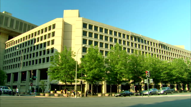 pedestrians and traffic pass the fbi headquarters building in washington, d.c. - fbi stock videos & royalty-free footage