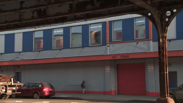 pedestrians and traffic passing in front of a self storage building during the day in the bronx as the reflection of an elevated subway train passing shows in the upper windows - self storage stock videos and b-roll footage