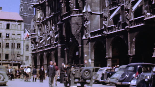 pedestrians and traffic passing new town hall / munich germany - anno 1945 video stock e b–roll