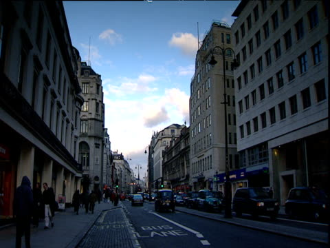 vidéos et rushes de pedestrians and traffic travel along busy oxford street as clouds pass in blue sky above london - oxford angleterre