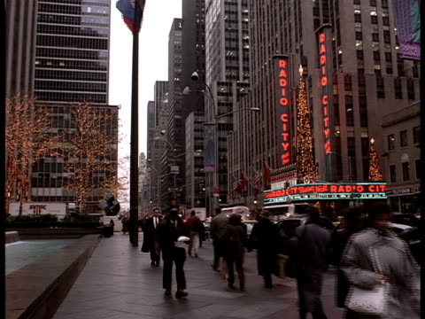 pedestrians and traffic travel down a city block in between a statue of giant christmas ornaments and radio music city hall. - radio city music hall stock videos & royalty-free footage