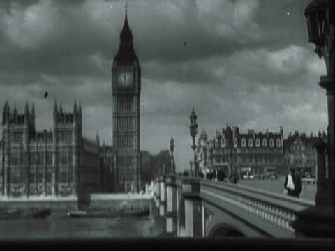vídeos de stock e filmes b-roll de ws pedestrians and vehicles crossing over bridge near big ben / london, england, united states - 1930
