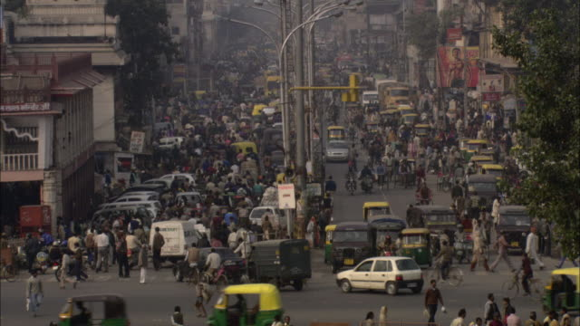 pedestrians and vehicles jam a busy delhi street. - population explosion stock videos & royalty-free footage