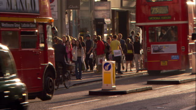pedestrians and vehicles move through a busy london intersection. - double decker bus stock videos & royalty-free footage