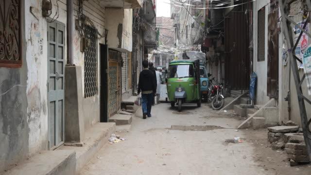 pedestrians and vehicles on narrow street - punjab pakistan bildbanksvideor och videomaterial från bakom kulisserna
