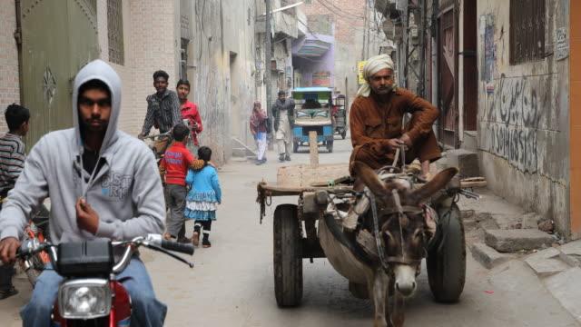 stockvideo's en b-roll-footage met pedestrians and vehicles on narrow street - lahore pakistan