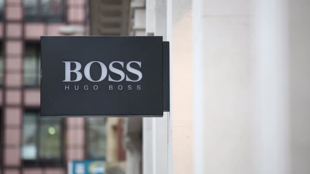 pedestrians and vehicles pass a hugo boss ag luxury clothes store in london, u k, on monday, nov 3 businessmen walk past a hugo boss store, general... - hugo boss stock videos & royalty-free footage