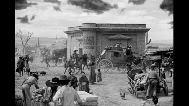 vidéos et rushes de pedestrians and wagon train on main street of very small western town / horses wagons stagecoaches driving through town adobe buildings under... - animaux au travail