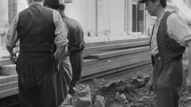 1939 montage pedestrians and workers in a city, air raid siren going off, people entering buildings and air raid shelters, closing doors, and leaving empty streets behind during world war ii / united kingdom - 1939 stock-videos und b-roll-filmmaterial