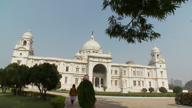 pedestrians approach victoria memorial in calcutta. - victoria memorial kolkata stock videos and b-roll footage