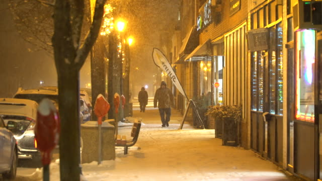 Pedestrians are out and about in Lindenhurst New York after dark as heavy snow begins to fall