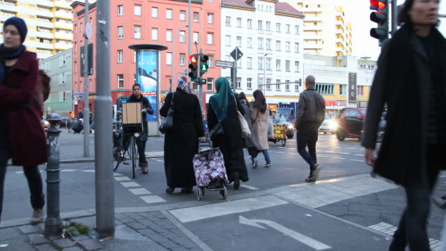 pedestrians are passing by at kottbusser tor in berlin kreuzberg a famous nightlife area and multi culture district with a lot of turkish shops bars... - kopftuch stock-videos und b-roll-filmmaterial