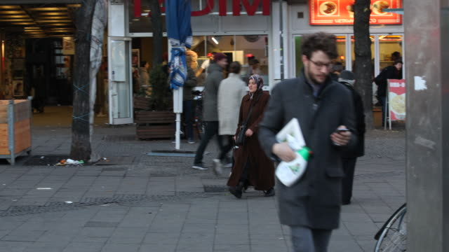 pedestrians are passing by at kottbusser tor in berlin - kreuzberg, a famous nightlife area and multi culture district with a lot of turkish shops,... - 懺悔点の映像素材/bロール