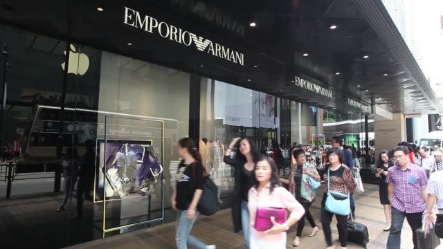 Pedestrians are reflected on a signage for Emporio Armani operated by Giorgio Armani SpA displayed at the companys store on Canton Road in the Tsim...