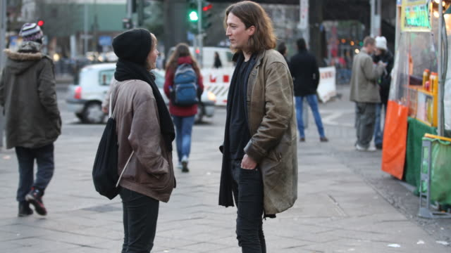 Pedestrians are standing and talking and passing by at Kottbusser Tor in Berlin Kreuzberg a famous nightlife area and multi culture district with a...