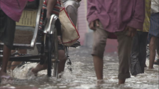 Pedestrians, bikes and cars travel on flooded road, Varanasi Available in HD.