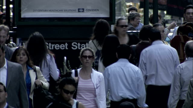 pedestrians briskly walk along the crowded sidewalk of wall street in new york city. available in hd. - wall street video stock e b–roll