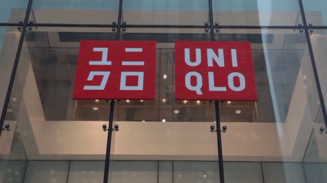 pedestrians carrying umbrellas walk past a uniqlo co store on 5th avenue in new york us on tuesday jan 21 close up of uniqlo signage on store front... - flagship store stock videos and b-roll footage