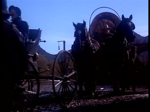 pedestrians clear out of the muddy streets of an old west town as a horse-drawn carriage leads a cattle drive through. - cattle drive stock videos & royalty-free footage