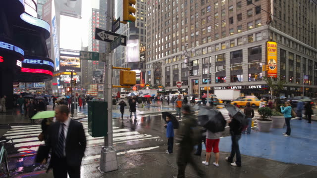 pedestrians cross 42nd street in manhattan on a rainy day. - 42nd street stock videos & royalty-free footage
