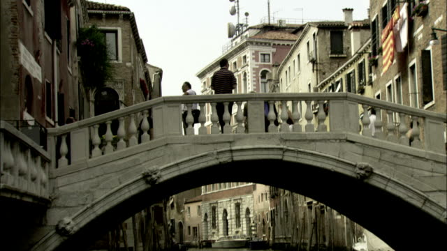 pedestrians cross a bridge that arcs over a venetian canal. available in hd. - ghetto video stock e b–roll