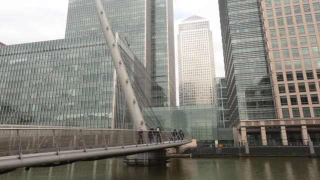 pedestrians cross a footbridge near the offices of jpmorgan chase co left and the one canada square office building center in the canary wharf... - establishing shot stock videos & royalty-free footage