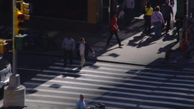 Pedestrians cross a New York City street.