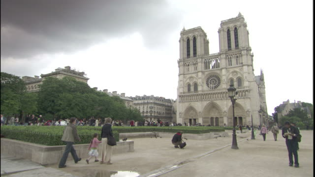 stockvideo's en b-roll-footage met pedestrians cross a plaza near the notre dame cathedral in paris. - stadsplein