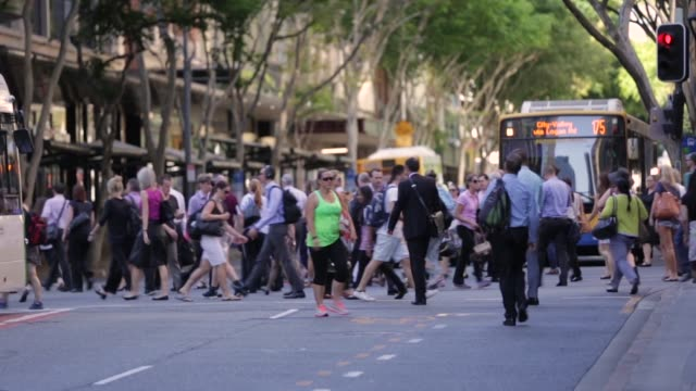 Pedestrians cross a road in Brisbane Australia on Tuesday Jan 12 Pedestrians wait at a crossing while traffic passes A bus waits as pedestrians cross...
