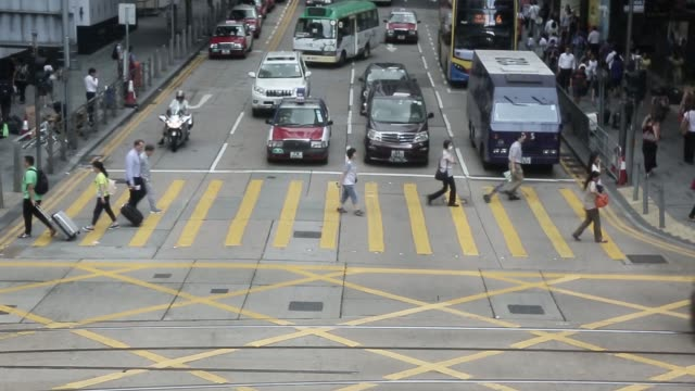 pedestrians cross a road in the central district of hong kong china on monday june 27 traffic pass pedestrians crossing a road in the central... - central district hong kong stock videos and b-roll footage