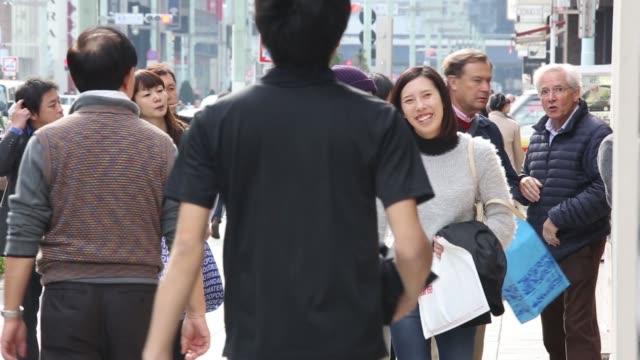 vídeos de stock, filmes e b-roll de pedestrians cross a road in the ginza district of tokyo japan on monday nov 17 pedestrians take pictures of a restaurant menu along a sidewalk... - produto interno bruto