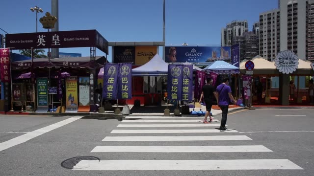 pedestrians cross a road outside the the zhuhai-macau border crossing in macau, l-r pedestrians crossing road, people get into a taxi after leaving... - leal senado square stock videos & royalty-free footage