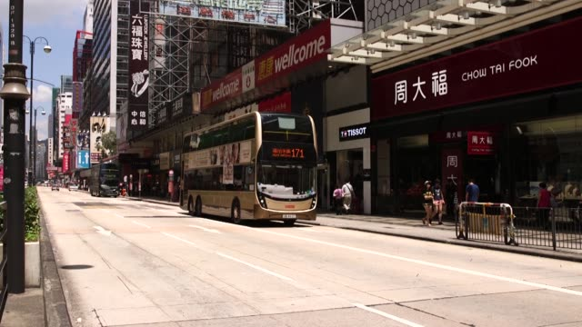 vidéos et rushes de pedestrians cross a road past traffic lights at a crossing in the mong kok district of hong kong china on monday sept 12 double decker buses drive... - mong kok