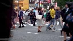 Pedestrians cross at Shibuya Crossing in Tokyo , Japan
