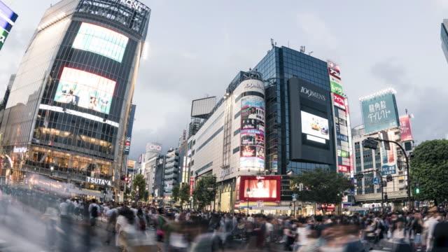 pedestrians cross at shibuya crossing, tokyo, japan - tokyo japan stock videos and b-roll footage