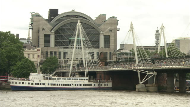 pedestrians cross hungerford bridge over river thames near charing cross. - hungerford bridge stock videos & royalty-free footage