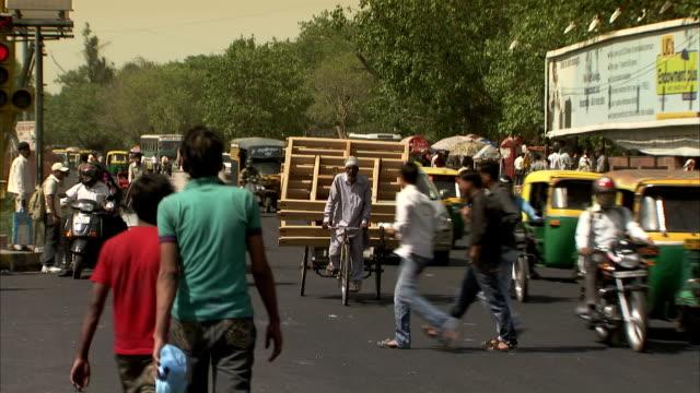 pedestrians cross in front of traffic on a busy street in delhi. - delhi stock videos & royalty-free footage